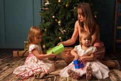 Mère heureuse à côté d'arbre de Noël avec des cadeaux Images libres de droits