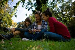 Mère heureuse à l'aide du téléphone portable avec ses enfants adolescents en nature image libre de droits