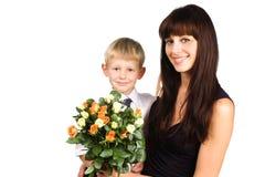Mère heureuse étreignant son fils avec des fleurs image stock