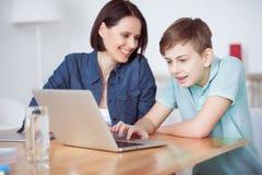 Mère heureuse aidant son fils à faire le travail Photo stock