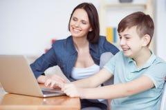 Mère heureuse aidant son fils à faire le travail image libre de droits