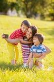 Mère heureuse avec deux enfants, prenant des photos en parc Images libres de droits