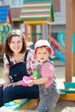 Mère heureuse avec l'enfant en bas âge dans le bac à sable Images stock