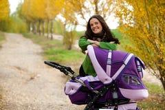 Mère heureuse avec la chéri dans la poussette Images libres de droits