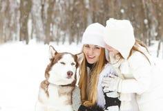 Mère heureuse avec la fille en parc d'hiver avec le chien de chiens de traîneau Images libres de droits