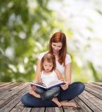 Mère heureuse avec la petite fille et le livre adorables Images stock