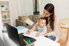 Mère heureuse avec le bébé et papiers fonctionnant à la maison Photos stock