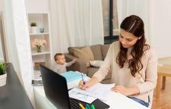 Mère heureuse avec le bébé et papiers fonctionnant à la maison Photographie stock libre de droits