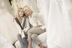 Mère heureuse avec le bras autour de sa fille s'asseyant dans le magasin nuptiale Image libre de droits