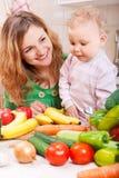 Mère heureuse avec le descendant de chéri préparant des légumes Images stock