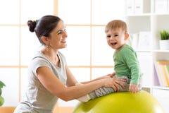 Mère heureuse avec le fils de bébé faisant la gymnastique sur la grande boule de forme physique dans le gymnase Photographie stock libre de droits