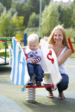 Mère heureuse avec le fils de deux ans sur le terrain de jeu Images libres de droits