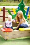 Mère heureuse avec le fils de deux ans sur le terrain de jeu Photographie stock