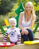Mère heureuse avec le fils de deux ans sur le terrain de jeu Photographie stock libre de droits