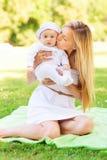Mère heureuse avec le petit bébé s'asseyant sur la couverture Photo libre de droits