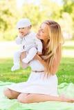 Mère heureuse avec le petit bébé s'asseyant sur la couverture Image libre de droits