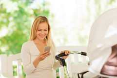 Mère heureuse avec le smartphone et la poussette en parc Images stock