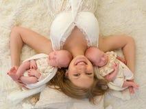 Mère heureuse avec les jumeaux identiques Photographie stock