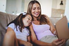 Mère heureuse avec sa fille à l'aide du comprimé numérique Photo libre de droits