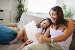 Mère heureuse avec sa fille à l'aide du comprimé numérique Photographie stock