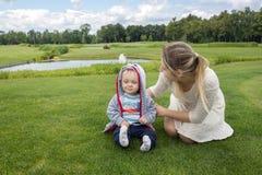 Mère heureuse avec ses 9 mois de bébé garçon détendant sur l'herbe à Photo stock