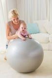 Mère heureuse avec son bébé dans la boule d'exercice Image libre de droits