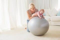 Mère heureuse avec son bébé dans la boule d'exercice Image stock