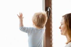 Mère heureuse avec son bébé garçon regardant la fenêtre Images stock