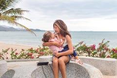 Mère heureuse avec un enfant s'asseyant sur la pierre près de la plage, ils embrassent et sourient photographie stock