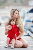 Mère heureuse avec une jeune fille près de club de yacht Images stock