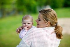 Mère heureuse ayant l'amusement avec la fille nouveau-née de bébé dehors Photos stock