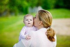 Mère heureuse ayant l'amusement avec la fille nouveau-née de bébé dehors Photographie stock libre de droits