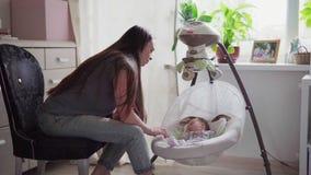 Mère heureuse basculant le berceau avec le bébé banque de vidéos