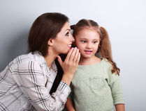 Mère heureuse chuchotant le secret à sa fille mignonne d'enfant dans l'oreille W Images stock