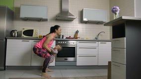 Mère heureuse d'ajustement faisant des postures accroupies soulevant le bébé à la maison clips vidéos