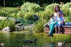 Mère heureuse de bonheur de famille embrassant tendrement ses enfants de deux fils le jour d'herbe au printemps, sentiments chaud Image stock