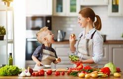Mère heureuse de famille avec le fils d'enfant préparant la salade végétale photos libres de droits