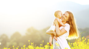 Mère heureuse de famille et étreindre et baiser de bébé en été sur le natur Images stock