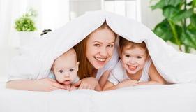 Mère heureuse de famille et deux enfants, fils et fille dans l'ONU de lit Photographie stock libre de droits