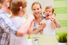 Mère heureuse de famille et enfant de fille balayant son toothb de dents Image libre de droits