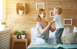 Mère heureuse de famille et enfant en bas âge de fils de bébé riant dans le lit Photographie stock libre de droits