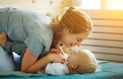 Mère heureuse de famille et enfant en bas âge de fils de bébé riant dans le lit Photos libres de droits