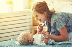 Mère heureuse de famille et enfant en bas âge de fils de bébé riant dans le lit Image libre de droits