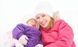 Mère heureuse de famille et fille de bébé jouant et riant dans la neige d'hiver Image libre de droits