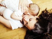 Mère heureuse de jeune brune tenant le fils de bébé d'enfant en bas âge, concept de allaitement, personnes modernes de mode de vi Photographie stock