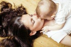 Mère heureuse de jeune brune tenant le fils de bébé d'enfant en bas âge, concept de allaitement, sourire moderne heureux de perso Photo stock