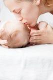 Mère heureuse embrassant un bébé, se trouvant sur un lit blanc Photos libres de droits
