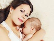 Mère heureuse en gros plan de portrait jeune et bébé de sommeil sur le lit à la maison photos libres de droits