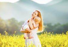 Mère heureuse et bébé de famille étreignant la nature en été Photo libre de droits