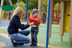 Mère heureuse et bébé garçon jouant sur le terrain de jeu Photo stock